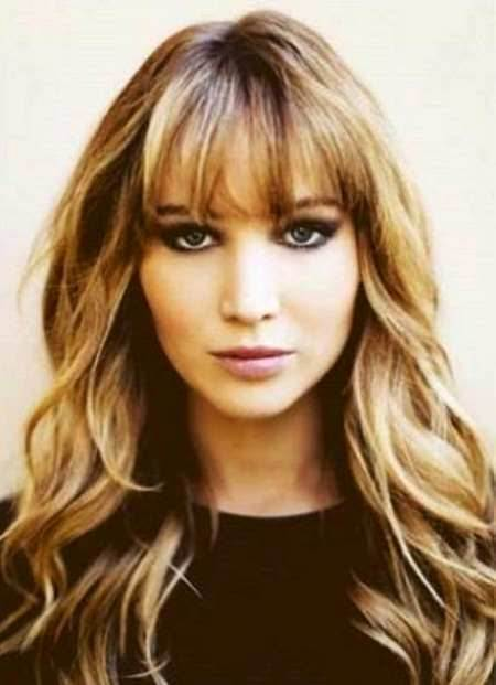 soft golden waves with thick bangs style curly hair